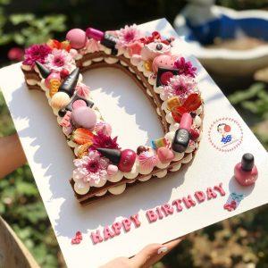 کیک حروف دخترانه با تم لوازم آرایشی